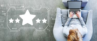 Five star rating with man using a laptop stock photography