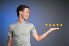 Five star rating or ranking, benchmarking concept. Man assesses service, hotel, restaurant. 5 star rating or ranking, benchmarking concept on blue background stock photos