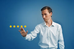Five star rating or ranking, benchmarking concept. Man assesses service, hotel, restaurant. 5 star rating or ranking, benchmarking concept on blue background royalty free stock photos