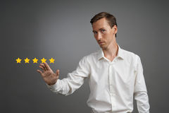 Five star rating or ranking, benchmarking concept. Man assesses service, hotel, restaurant. 5 star rating or ranking, benchmarking concept on grey background royalty free stock photography