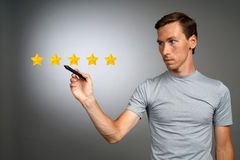 Five star rating or ranking, benchmarking concept. Man assesses service, hotel, restaurant. 5 star rating or ranking, benchmarking concept on grey background stock photos
