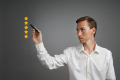 Five star rating or ranking, benchmarking concept. Man assesses service, hotel, restaurant. 5 star rating or ranking, benchmarking concept on grey background stock image