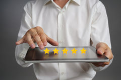 Five star rating or ranking, benchmarking concept. Man with tablet PC assesses service, hotel, restaurant. 5 star rating or ranking, benchmarking concept on grey stock images