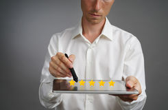 Five star rating or ranking, benchmarking concept. Man with tablet PC assesses service, hotel, restaurant. 5 star rating or ranking, benchmarking concept on grey royalty free stock images