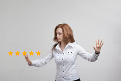 Five star rating or ranking, benchmarking concept. Woman assesses service, hotel, restaurant. 5 star rating or ranking, benchmarking concept on grey background stock image