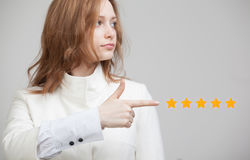 Five star rating or ranking, benchmarking concept. Woman assesses service, hotel, restaurant. 5 star rating or ranking, benchmarking concept on grey background royalty free stock photography