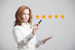Five star rating or ranking, benchmarking concept. Woman assesses service, hotel, restaurant. 5 star rating or ranking, benchmarking concept on grey background royalty free stock photo