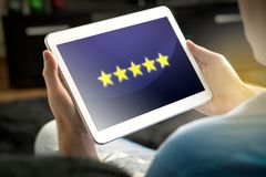 Five star rating and review from satisfied and happy customer an. D reviewer. Man holding tablet with an imaginary criticism application, social media or website Royalty Free Stock Photos