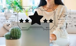 Five star rating with woman using her laptop stock photos