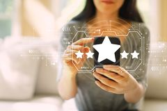 Five star rating with woman using a smartphone stock photo
