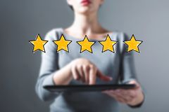 Five star rating with woman using a tablet. Five star rating with business woman using a tablet computer stock photos