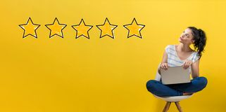 Five star rating with woman using a laptop royalty free stock photo