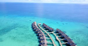 Five 5 star resort water bungalows in Maldives with drone aerial flying view on white sand beach on tropical. Island Stock Image