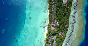 Five 5 star resort water bungalows in Maldives with drone aerial flying view on white sand beach on tropical Royalty Free Stock Image