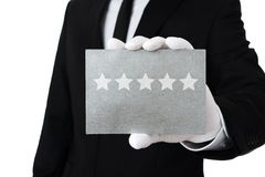 Five star service. Human hand holding silver card with five stars on it Stock Image