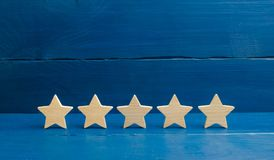 Five stars on a blue background. The concept of rating and evaluation. The rating of the hotel, restaurant, mobile application. Qu royalty free stock images