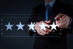Five stars 5 rating with a businessman. Is touching virtual computer screen.For positive customer feedback and review with excellent performance royalty free stock image