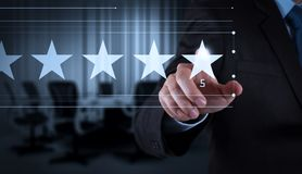 Five stars 5 rating with a businessman is touching virtual computer. Screen.For positive customer feedback and review with excellent performance royalty free stock photo