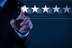 Five stars 5 rating with a businessman is touching virtual computer. Screen.For positive customer feedback and review with excellent performance royalty free stock photography