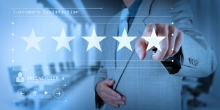 Five stars 5 rating with a businessman is touching virtual computer screen stock photo