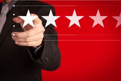 Five stars 5 rating with a businessman is touching virtual computer screen. For positive customer feedback and review with excellent performance stock photo