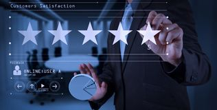 Five stars 5 rating with a businessman is touching virtual computer screen. For positive customer feedback and review with excellent performance stock image