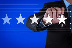 Five stars 5 rating with a businessman. Is touching virtual computer screen.For positive customer feedback and review with excellent performance stock images