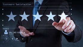 Five stars 5 rating with a businessman is touching virtual computer screen.For positive customer. Feedback and review with excellent performance stock photos