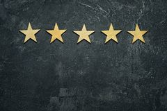 Five stars. In a row on a black rustic cement boards. Conceptual of service rating and quality of trade. Top view, copy space for your text Stock Photography