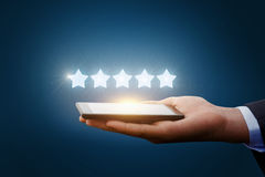 Five stars from a tablet. Five stars from a tablet in the hands businessman royalty free stock image