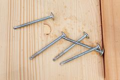 Five steel screws on a wooden plank Stock Photo