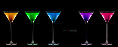 Five Stemmed Cocktail Glasses Full of Colored Liquors. Template Stock Photography