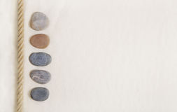 Five stones in the beige sand. Background for summer holiday con Stock Images