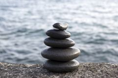 Five stones cairn tower, rock zen sculpture, black pebbles and ocean light blue background. Harmony and balance still life royalty free stock images
