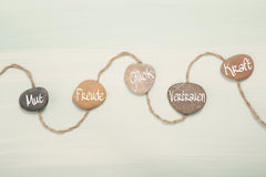 Five stones with german text for: courage, happiness, luck, trus. T and power Stock Photos