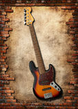 Five string bass guitar. With brick wall royalty free stock photography