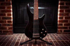 Five string bass guitar in front of fireplace Stock Photos