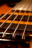 Five String Bass Up. Angle shot of a 5 string bass in an angle with selective focus strings above 2nd soapbar pickup. - one of few honey finish 5 string bass Stock Images