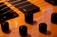 Five String Bass Up Knobs. Angle shot of a 5 string bass in an angle with selective focus on the middle tuner knob. - one of few honey finish 5 string bass shots Stock Photos