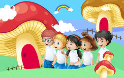 Five students near the giant mushroom houses Royalty Free Stock Photos