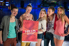Five stylish young people with a banner. At the party royalty free stock photography