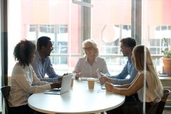 Five diverse businesspeople sitting in boardroom and negotiating. Five successful positive businesswomen and businessmen different age and ethnicity sitting in stock image