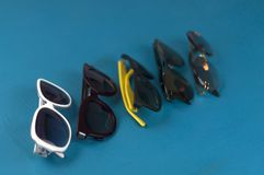 five sunglasses in different designs and colors royalty free stock photography