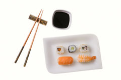 Five sushi rolls and chopsticks. Sushi rolls. From left to right, top to bottom: California roll carrot, Makizushi cucumber, California roll, Nigiri Sushi salmon Stock Image