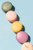 Five sweet colorful macaroons on blue table background. Royalty Free Stock Image