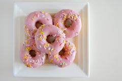 Five Sweet Pink Doughnuts Confection Served on a Square White Pl stock photos