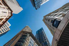 Five tall buildings upright. Five tall buildings viewed from bottom looking up with blue sky during the day Royalty Free Stock Photo