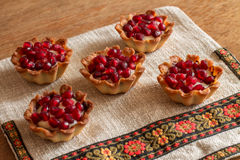 Five tartletes with custard and pomegranate Royalty Free Stock Images