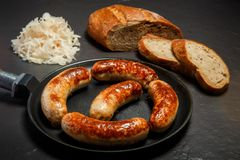 Five tasty ruddy juicy sausages fried in large frying pan. Five appetizing ruddy juicy sausages fried in large frying pan served with sliced rye bread and stock image