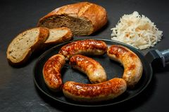 Five tasty ruddy juicy sausages fried in large pan. Served with sliced rye bread and sauerkraut on black background royalty free stock photos